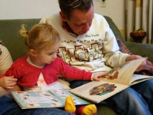 man reading to toddler